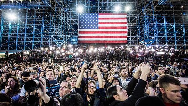 Javis Center Il est 2 heures du matin au Javis Center où sont réunis les supporters d'Hillary Clinton. Sachant sa défaite, de nombreux supporters sont rentrés chez eux et il ne reste plus qu'une petite partie réunie devant le pupitre où l'on attend Hillary. Elle ne se présentera pas le soir même, c'est John Podesta qui se présentera au pupitre pour parler aux supporters. Cette photo est prise quand après une longue attente il se présente enfin. Quand la foule se dispersera, je remarquerai l'équipe de Quotidien à côté de moi qui a couvert l'événement en Live toute la nuit en France.