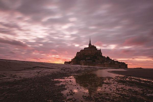 Ce paysage a été réalisé au Mont Saint-Michel en 2015, après une soirée très calme au niveau du ciel, ce dernier s'est rosé et malgré la marée basse, un léger reflet m'a permis d'obtenir cette vue. Canon EOS 6D – EF16-35mm f/2.8L II USM – 16mm – 20s f/8 – 640ISO